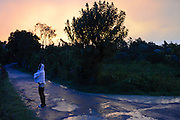 A woman pauses on the road outside Rancho Baiguate, an ecotourism resort, following a hard summer storm at dusk. June 11, 2013, Jarabacoa, Dominican Republic.