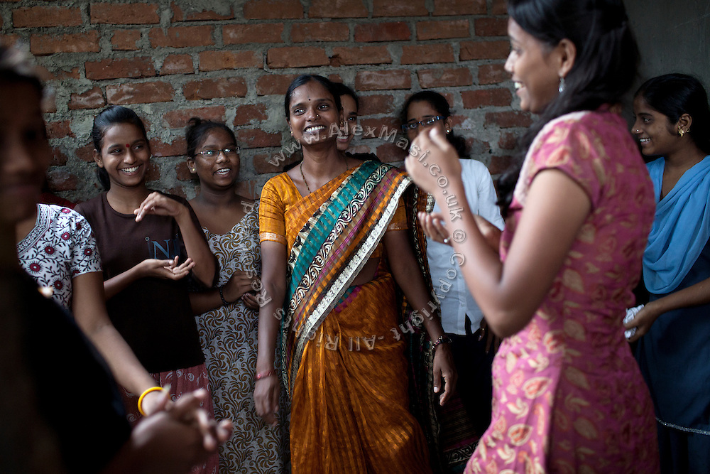 Anita Suresh Kasbe, 41, (centre) the Unicef community facilitator is dancing and singing with the girls attending the Unicef-run 'Deepshikha Prerika' project inside the Milind Nagar Pipeline Area, an urban slum on the outskirts of Mumbai, Maharashtra, India. Here, Mayuri Mahesh Pandit, 13, (left) she resides with her family.