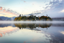 © Licensed to London News Pictures. 15/10/2018. Keswick UK. Derwent Isle on Derwentwater is shrouded in mist at dawn this morning on a cold start to the day in Keswick, Cumbria. Photo credit: Andrew McCaren/LNP