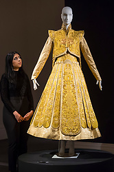 "© Licensed to London News Pictures. 25/10/2019. LONDON, UK. A staff member poses with a ""Gold Chinese traditional bridal dress"" by Guo Pei (Est.  GBP500-700k).  Preview of ""GOLD: The Midas Touch"" at Sotheby's in New Bond Street.  Artworks spanning six centuries dedicated to gold will be offered for sale on 29 October.  Photo credit: Stephen Chung/LNP"