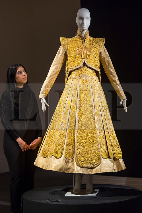 """© Licensed to London News Pictures. 25/10/2019. LONDON, UK. A staff member poses with a """"Gold Chinese traditional bridal dress"""" by Guo Pei (Est.  GBP500-700k).  Preview of """"GOLD: The Midas Touch"""" at Sotheby's in New Bond Street.  Artworks spanning six centuries dedicated to gold will be offered for sale on 29 October.  Photo credit: Stephen Chung/LNP"""