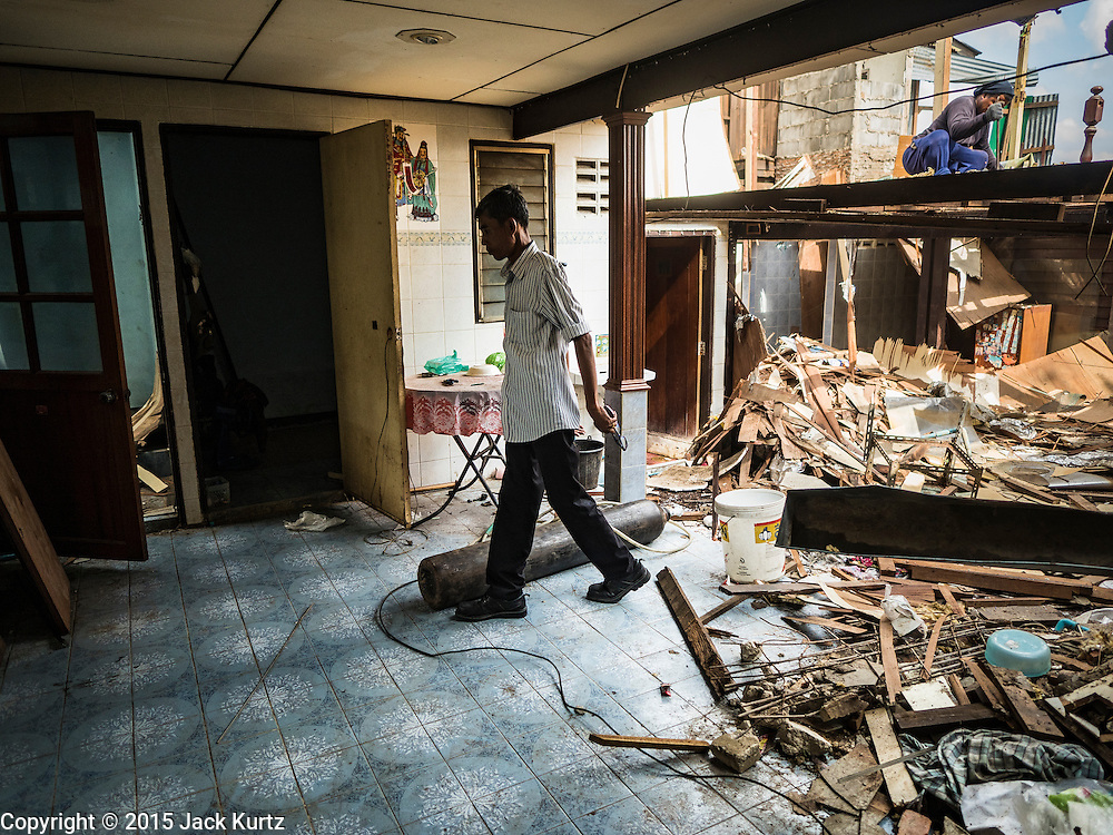 12 NOVEMBER 2015 - BANGKOK, THAILAND:  A man walks through a house being torn down at Wat Kalayanmit. Fifty-four homes around Wat Kalayanamit, a historic Buddhist temple on the Chao Phraya River in the Thonburi section of Bangkok, are being razed and the residents evicted to make way for new development at the temple. The abbot of the temple said he was evicting the residents, who have lived on the temple grounds for generations, because their homes are unsafe and because he wants to improve the temple grounds. The evictions are a part of a Bangkok trend, especially along the Chao Phraya River and BTS light rail lines. Low income people are being evicted from their long time homes to make way for urban renewal.       PHOTO BY JACK KURTZ