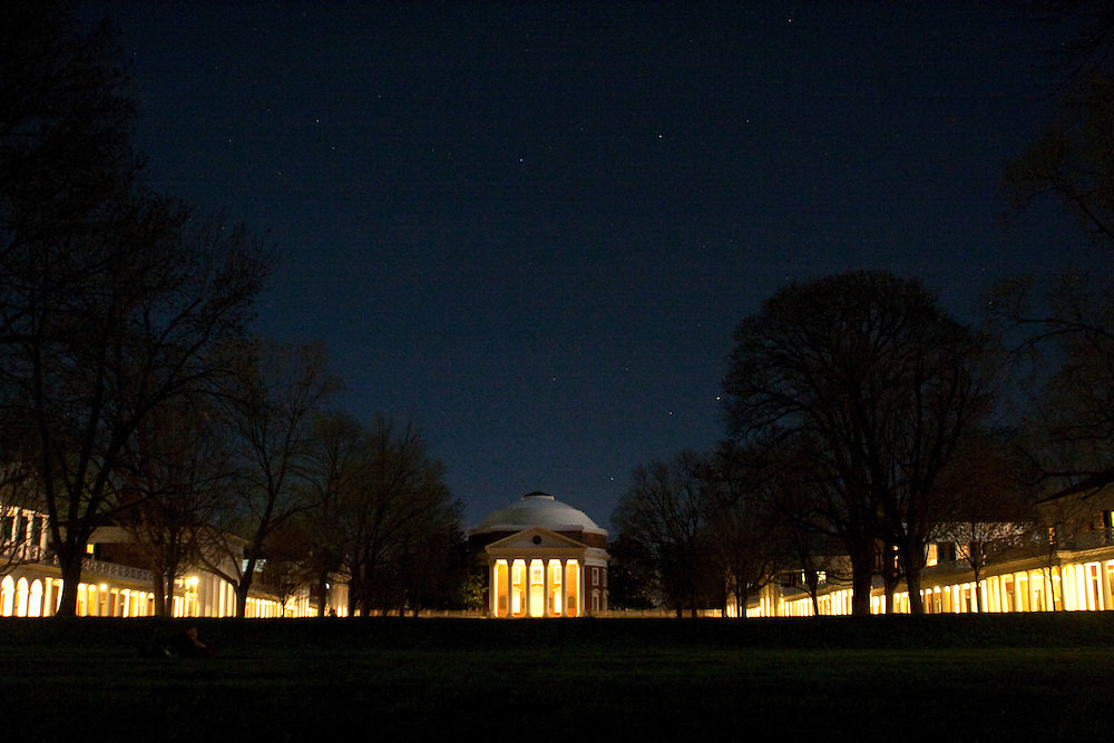 The rotunda, lawn and pavilions of the University of Virginia, photographed at night, with stars visible.