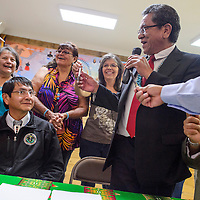 Navajo Nation President Russell Begaye gets a pen from Ina Noggle after asking the crowd to loan him a pen for the signing of a contract for the purchase of the Red Barn Liquors property in Sanders during a signing ceremony at the Nahata Dzil Chapter House Thursday.