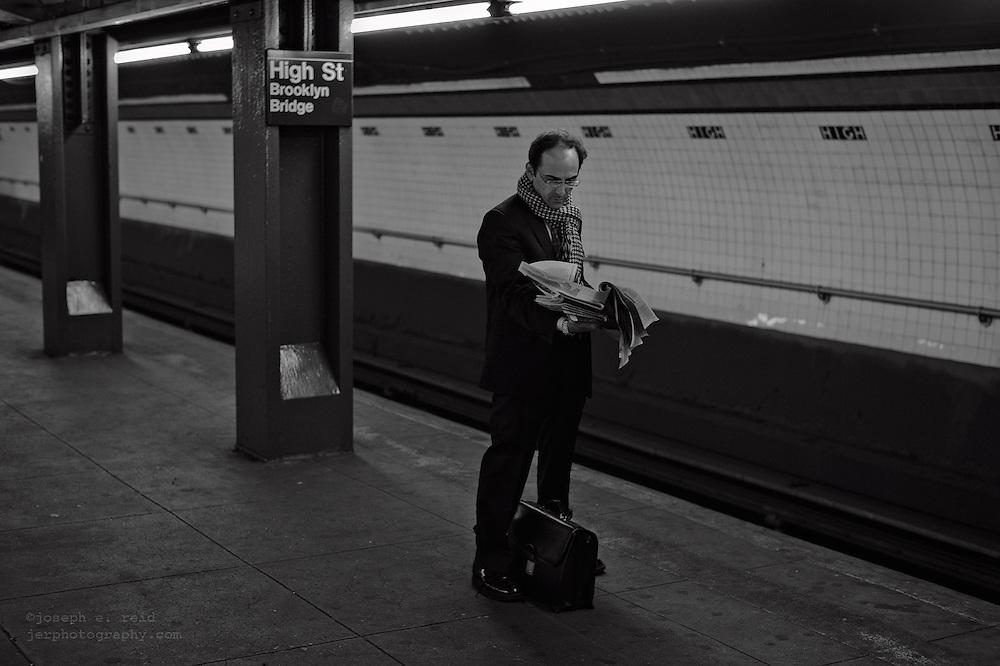 Man reading newspaper while waiting for subway, Brooklyn, NY, US