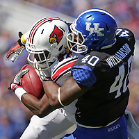 UK linebacker Avery Williamson tackles U of L running back Senorise Perry in the first half as the University of Kentucky plays the University of Louisville at Commonwealth Stadium in Lexington, Ky. Saturday Sept. 14, 2013. Photo by David Stephenson