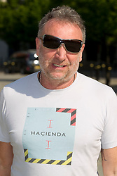 "© Licensed to London News Pictures. 22/05/2012. Manchester, UK. Musician, Peter Hook, walks through Manchester in the sunshine, wearing sunglasses and a t-shirt which reads ""Hacienda"". Last night, the bass player from New Order and Joy Division, known to fans as ""Hooky"", celebrated one last rave at a special Hacienda event in the city. Photo credit : Joel Goodman/LNP"