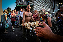 Member of the Donetsk People's Republic militias carries tray with bread for the locals which hide in the shelter after their houses was devastated by Ukrainian army shelling in Ilovaysk (50km from Donetsk), Ukraine, 14 August 2014. Town Ilovaysk was destroyed by Ukranian army's shelling during last two weeks. More than two thousand people all night and day live in their shelter. They haven't water, <br />