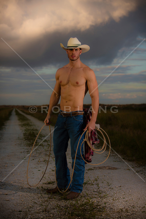 shirtless cowboy standing on a dirt road with a lasso in his hand