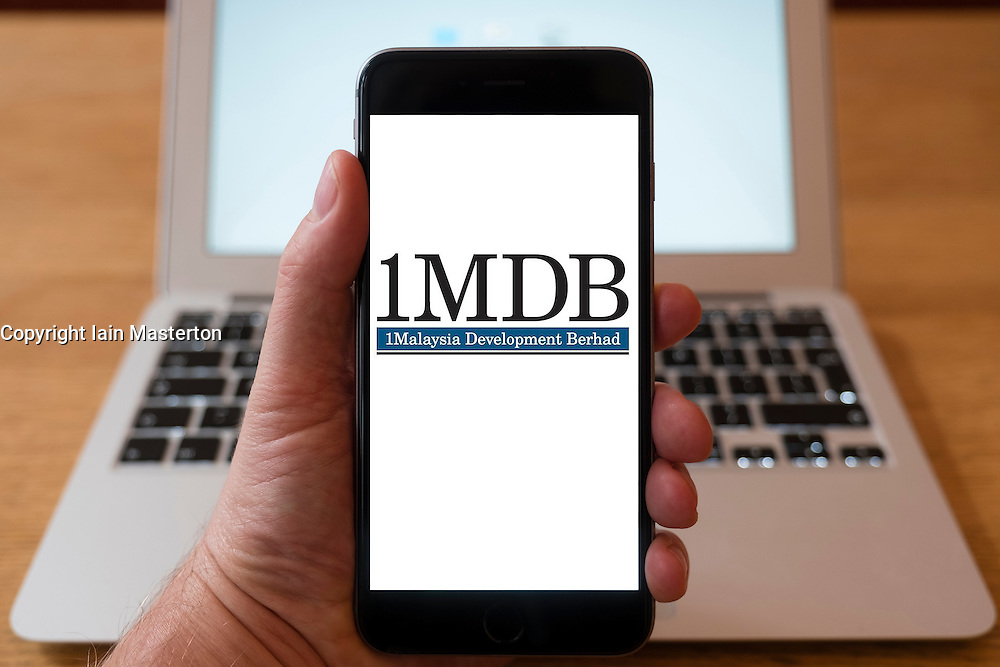 Using iPhone smartphone to display logo of Malaysian strategic development fund  1MDB
