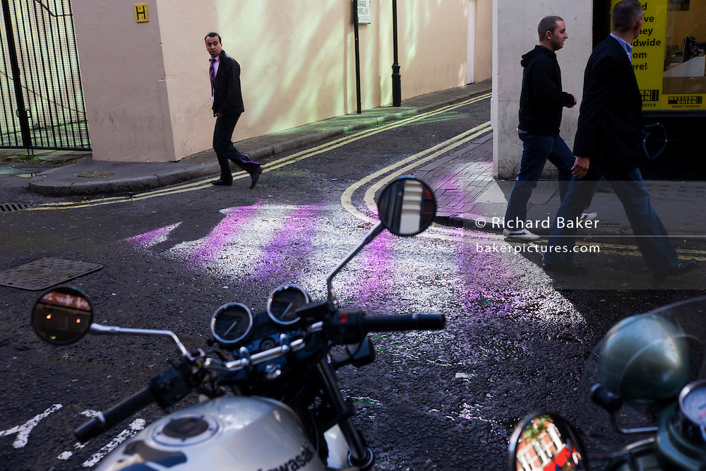Pedestrians in a Soho side-street, pattened with purple.