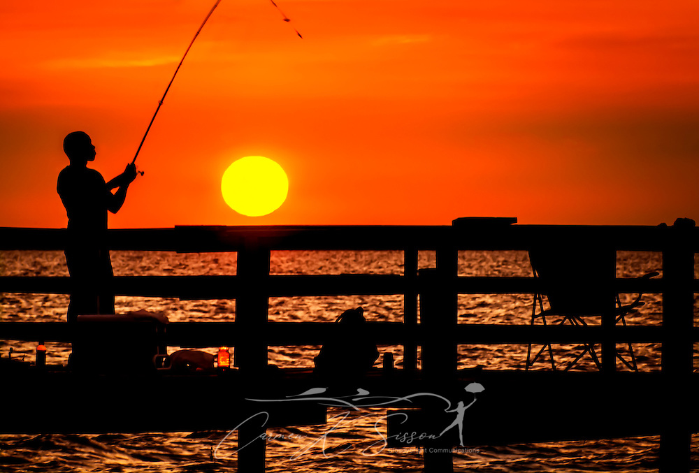 A man is silhouetted by the setting sun as he fishes July 1, 2013, at Cedar Point Fishing Pier on the Alabama Gulf Coast. (Photo by Carmen K. Sisson/Cloudybright)