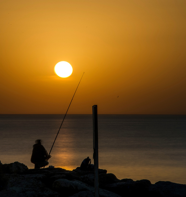 Fisherman silhouette agains sunset on Tel Aviv beach