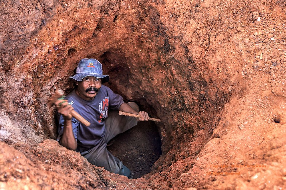 Digging a Hole: Promises of white gold compels this miner to daily risk his life digging dangerous, unsupported shafts, often to a depth of 8 meters with no safety precautions, near Kuta Beach, Lombok Indonesia.