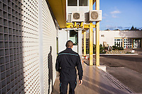 LECCE, ITALY - 10 NOVEMBER 2016: A penitentiary guard walks towards the command room of the largest penitentiary in the southern Italian region of Apulia, holding 1,004 inmates in the outskirts of Lecce, Italy, on November 10th 2016.<br /> <br /> Here a group of ten high-security female inmates and aspiring sommeliers , some of which are married to mafia mobsters or have been convicted for criminal association (crimes carrying up to to decades of jail time), are taking a course of eight lessons to learn how to taste, choose and serve local wines.<br /> <br /> The classes are part of a wide-ranging educational program to teach inmates new professional skills, as well as help them develop a bond with the region they live in.<br /> <br /> Since the 1970s, Italian norms have been providing for reeducation and a personalized approach to detention. However, the lack of funds to rehabilitate inmates, alongside the chronic overcrowding of Italian prisons, have created a reality of thousands of incarcerated men and women with little to do all day long. Especially those with a serious criminal record, experts said, need dedicated therapy and professionals who can help them.