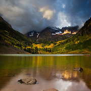 The sun breaks through the autumn clouds on Maroon Lake in Maroon Bells Snowmass Wilderness.