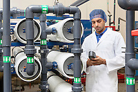 Worker holding an equipment in bottling plant