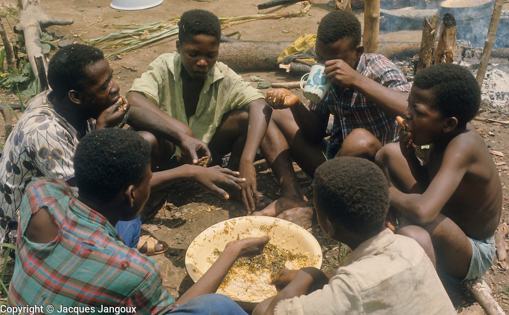 Lunch during communal work in the field by Kpelle men. The Kpelle language belongs to the Niger-Congo language family, subfamily Mande.