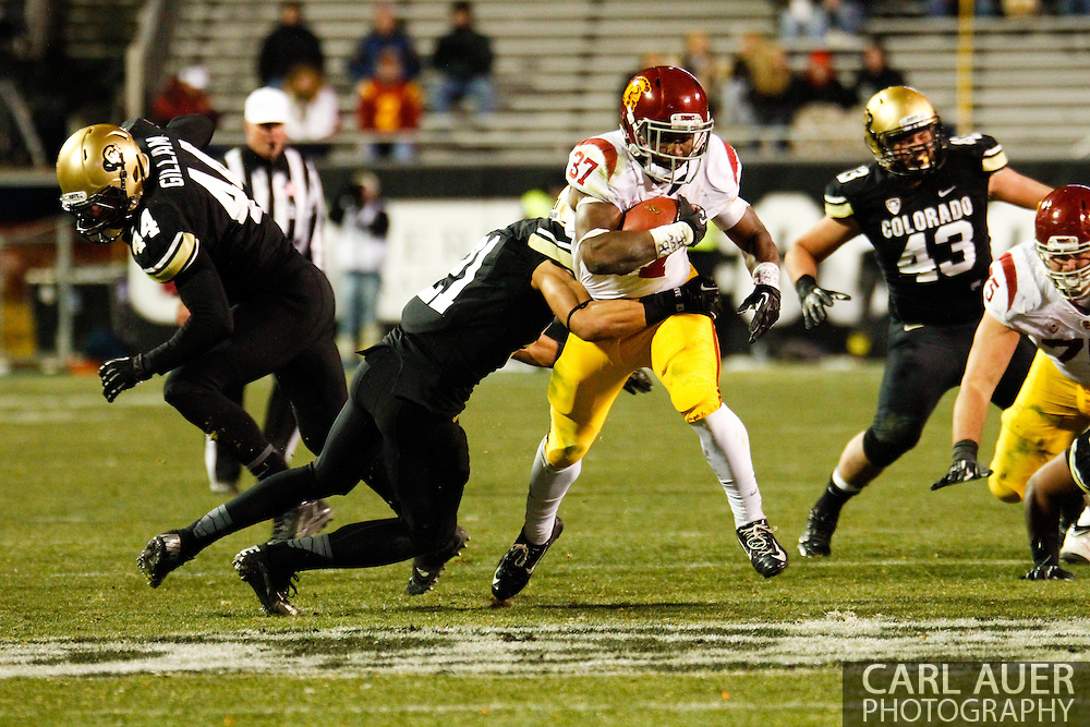 November 23rd, 2013: USC Trojans sophomore running back Javorius Allen (37) tries to break a tackle by Colorado Buffaloes junior defensive back Jered Bell (21) in the third quarter of the NCAA Football game between the University of Southern California Trojans and the University of Colorado Buffaloes at Folsom Field in Boulder, Colorado