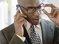 Businessman using mobile phone indoors (close-up)