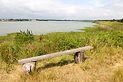Summer landscape view of bench overlooking  River Deben tidal estuary, Sutton, Suffolk, England, UK