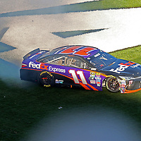 Denny Hamlin (11) spins on the grass after winning the 58th Annual NASCAR Daytona 500 auto race at Daytona International Speedway on Sunday, February 21, 2016 in Daytona Beach, Florida.  (Alex Menendez via AP)