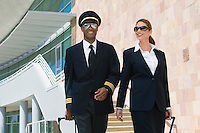 Pilot and flight attendant walking outside building