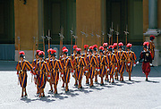 The traditional Vatican guards in St Peter's Square in Vatican City in their ornate yellow blue and red uniforms