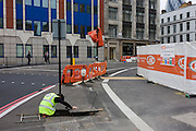 Contractor inspects underground cabling within manhole in a London street.