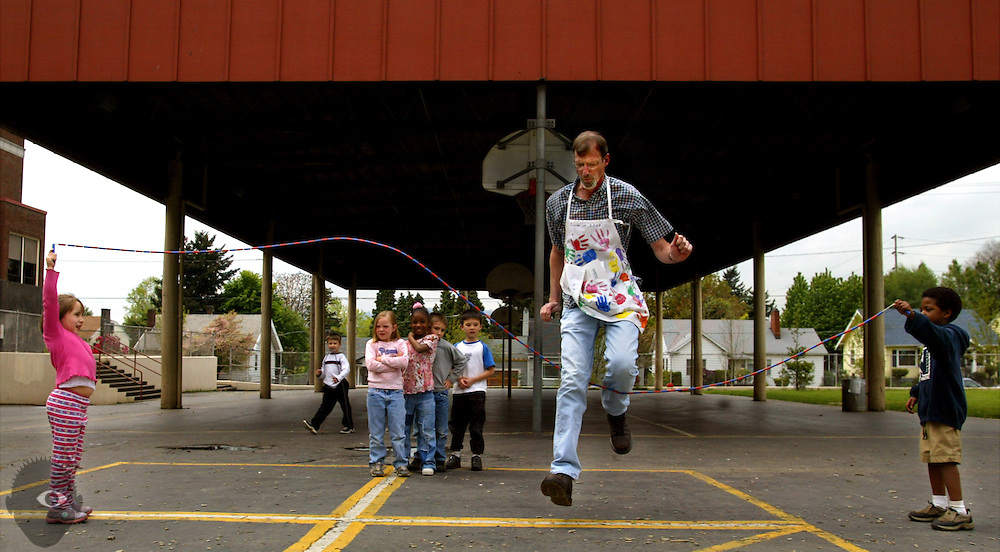 May 12, 2003 -   Kindergarten teacher Bob Parker (center) takes in some jump roping during recess at Grout Elementary School in Portland, Oregon. He is the talles teacher in the school working with the smallest kids but they all adore him just the same.