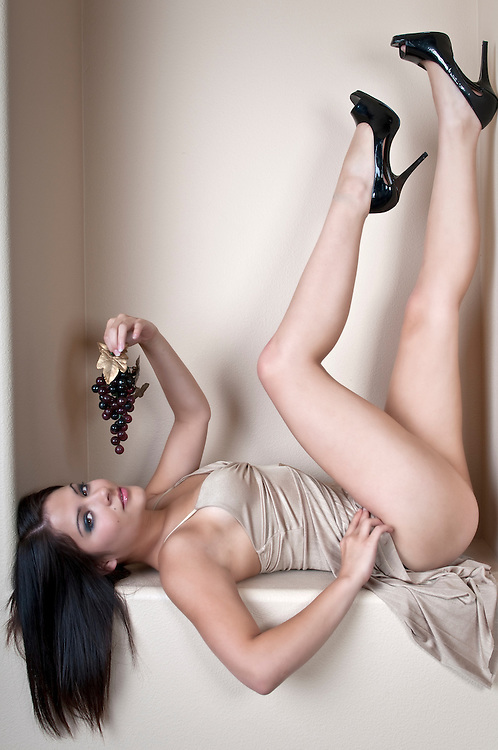 Young brunette posing very sexy in night dress, playing with grapes.