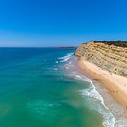 Aerial seascape, of Praia Porto de Mos (Beach and seaside cliff formations along coastline of Lagos city), famous destination in Algarve. South Portugal.