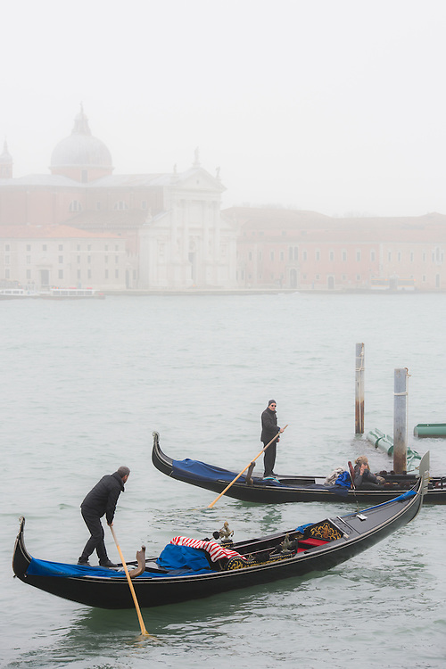 Two gondoliers are seen approaching the entrance of the mooring at St Mark's Square on a misty day in Venice. Cimitero di San Michele can be seen in the background.