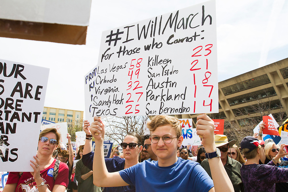 A student holds a sign up with a tally of those who have been shot and killed during school shootings during the March for Our Lives event in front of Dallas City Hall on Saturday.