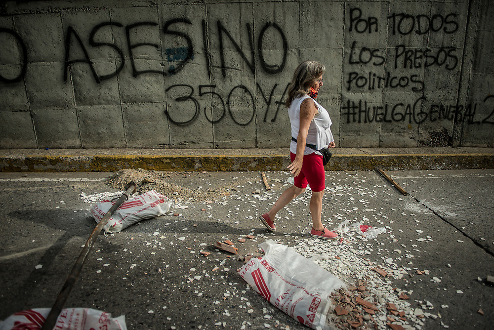 CARACAS, VENEZUELA - JULY 27, 2017: A woman walks down a road blocked with bags of construction debris, in support of a national strike, called by the political opposition to last for  48 hours, all day July 26th and 27th. They called for their supporters to close businesses, not go to work, and instead create barricades to block off their streets.  Opposition controlled areas of the country were completely shut down.  The strike was called as part of the opposition's civil resistance movement - that began on April 1st, to protest against the Socialist government's attempt to elect a new constituent assembly that will have the power to re-write the constitution, and will threaten democracy.  PHOTO: Meridith Kohut for The New York Times