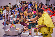 10 AUGUST 2012 - PHOENIX, AZ: A Hindu priest helps a family make an offering to a diety during the celebration of Janmashtami at Ekta Mandir, a Hindu temple in central Phoenix. Janmashtami is the Hindu holy day that celebrates the birth of Lord Krishna. Hindu communities around the world celebrate the holy day. In Arizona, most of the Hindu temples in the Phoenix area have special celebrations of the day.    PHOTO BY JACK KURTZ