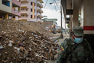 2016/08/05 – Portoviejo, Ecuador: A soldier passes by some derelict buildings in Portoviejo's centre, Ecuador, 5th August 2016. He uses a mask to avoid breathing the dust that fills the air, after so many buildings collapsed. Portoviejo's town centre is closed to the public and secured by the army since most of its building were heavily damaged by the earthquake, turning it into a ground zero area. (Eduardo Leal)