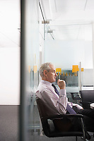 Mature businessman sitting in conference room side view