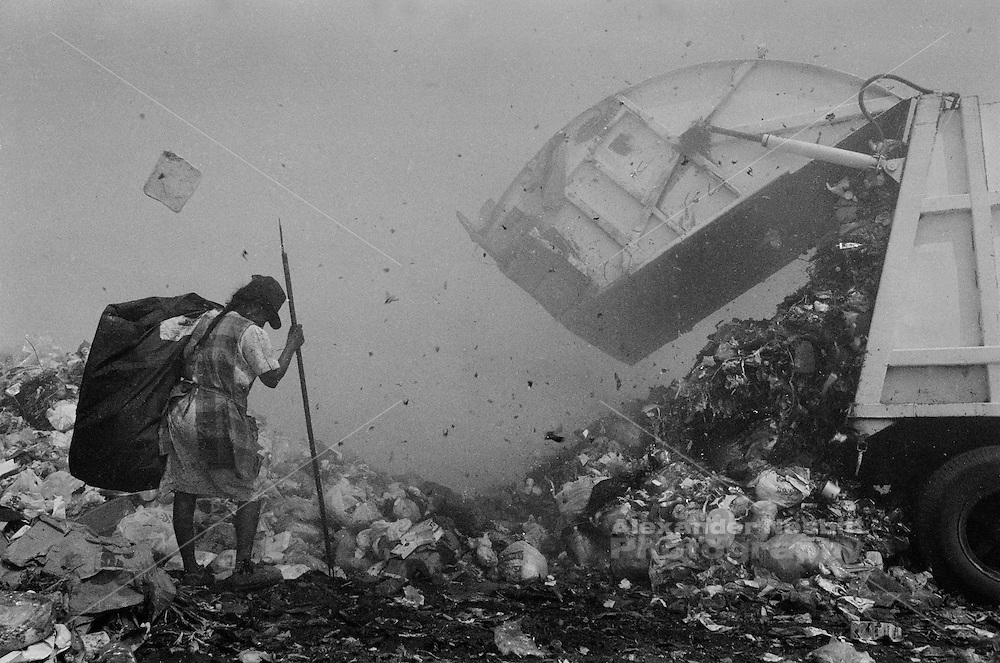 Municipal dump, Oaxaca, Mexico 1998 - A woman braces herself amidst the wind and smoke of the dump as a garbage truck expels new waste.  She is hoping to be first to pick though the garbage to scavenge materials she can sell for recycling. ..In the municipal dump a self governed group of 80 individuals and families eke out a living.  Los Pepenadors (the Pickers) work in a landscape of garbage and flames, blanketed by toxic smoke, along side bulldozers and garbage trucks.  They do the impossible job of recycling what the rest of their society can't be bothered to deal with. ...