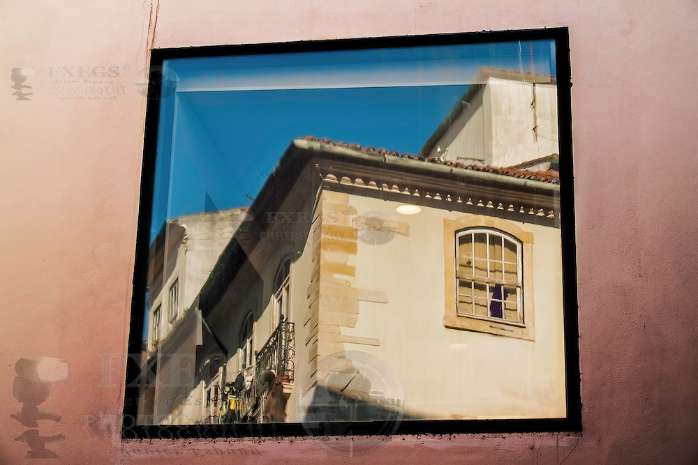 Coimbra, December 2012. Building reflected on a window in downtown
