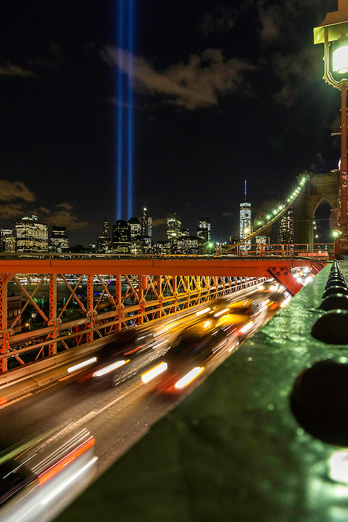 The 911 Memorial lights shine brightly in the night sky over Manhattan as seen from the Brooklyn Bridge on September 11th.