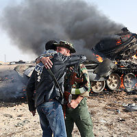 Rebel fighters embrace in front of a burning tank in the town of Ajdabiya, Libya, following allied airstrikes ealier in the day and the retreat of Col. Muammar el-Qaddafi's forces. March 2011.