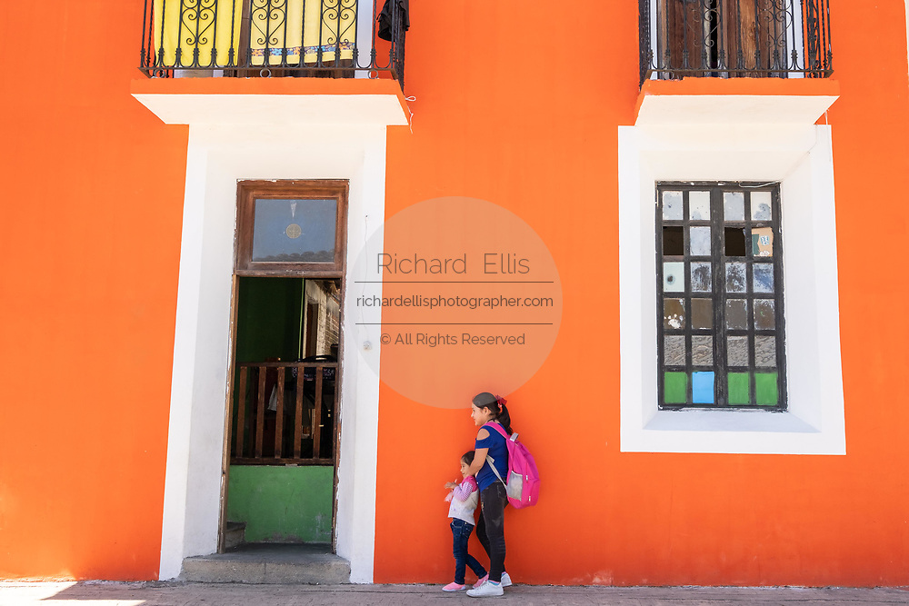 A Mexican woman and her daughter wait for a bus in front of a brightly painted orange building in Xico, Veracruz, Mexico.