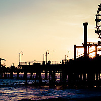 Santa Monica Pier Sunset Retro Panoramic Photo. Panorama picture ratio is 1:3.  Santa Monica Pier is a landmark located in Los Angeles county that has an amusement park with a ferris wheel, roller coaster, restaurants, and other attractions.