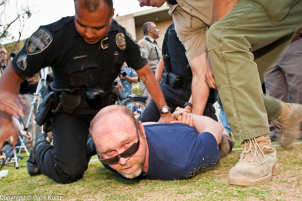 15 APRIL 2011 - PHOENIX, AZ: Arizona State Police and Capitol Police arrest a man at a Tea Party rally in Phoenix, AZ, Friday. About 500 supporters of the Tea Party movement rallied Friday at the Arizona State Capitol to mark tax day. They protested high taxes, the federal deficit, the debt limit and immigration policy. About 50 pro-immigrant protesters held a counter rally at the capitol. At least one person was arrested, and others led away by police after several shouting matches between Tea Party supporters and the immigrants rights protesters broke out.     Photo by Jack Kurtz