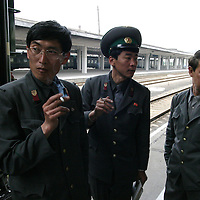 NORTHERN CHINA-APRIL 25: North Korean soldiers talk April 25, 2004 next to a train bound for Pyongyang in Dandong, Liaoning province, China. At least 154 people died, 76 of whom are confirmed children and more than 1300 were injured in a train explosion in Ryonchon, a North Korean town 20 km across the Dandong border. China said on Saturday it would give North Korea $1.21 million worth of medical supplies, tents, and food to help it cope with the train disaster in Ryongchon.