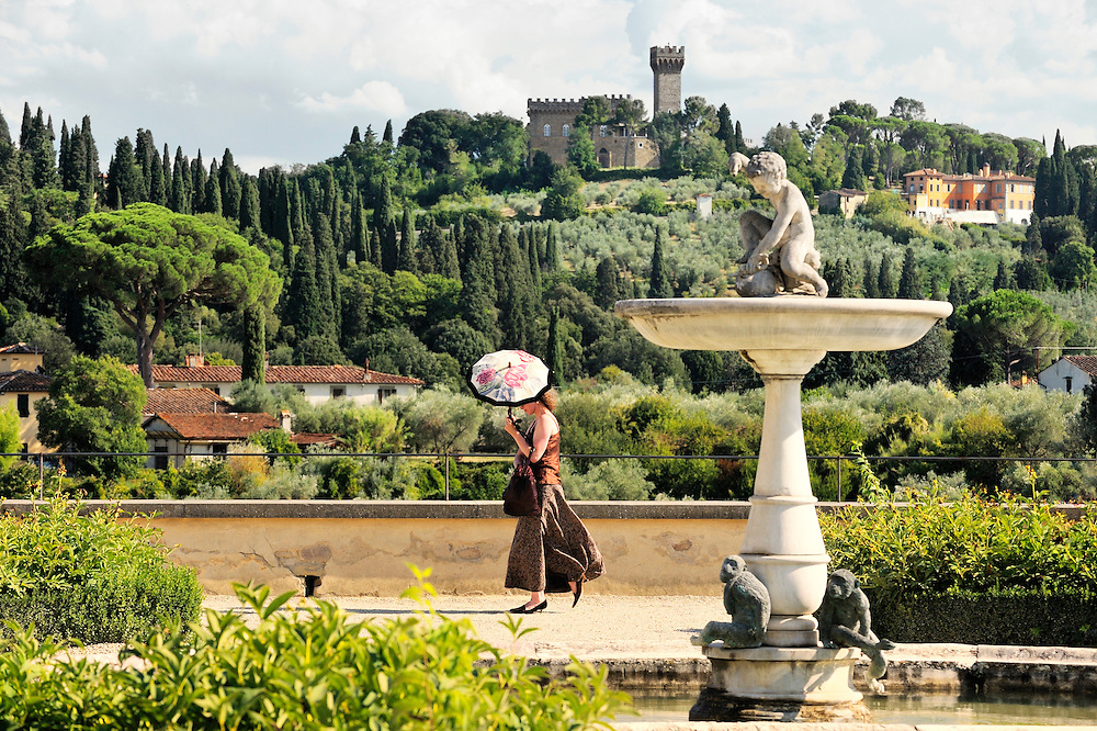Florence, Tuscany, Italy. South from the upper terrace or Knight's Garden of the Boboli Gardens. Young woman with parasol