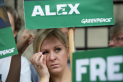 © London News Pictures. 05/10/2013.  London, UK. A friend of  arrested Greenpeace activists Alex Harris wipes a tear from her eye during the demo.  Supporters of Greenpeace stage a demonstration outside the Russian Embassy in London to protest against the arrest of 30 Greenpeace activists, known as the 'Arctic 30' who charged with piracy by a Russian court, following a peaceful protest against Arctic oil drilling at an oil platform in the Pechora Sea. Photo credit Ben Cawthra/LNP
