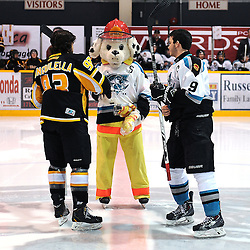 iLINDSAY, ON - Feb 7 : Ontario Junior Hockey League Game Action between the Lindsay Muskies and the Aurora Tigers , Sparky the Fire Dog with Vince Herlihey #9 of the Lindsay Muskies Hockey Club and Robert Angiolella #93 of the Aurora Tigers Hockey Club during the pre-game ceremony.<br /> (Photo by Andy Corneau / OJHL Images)