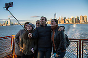 A family group of tourists pose and smile for a selfie photograph at the back of Staten Island Ferry travelling away from Lower Manhattan, which can be seen in the background,Upper Bay, New York City, New York, United States of America. (photo by Andrew Aitchison / In pictures via Getty Images)